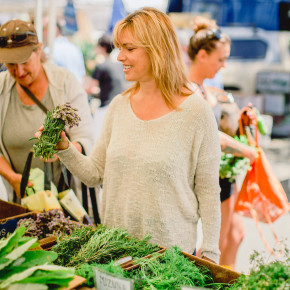 Melanee at the market holding a bunch of greens
