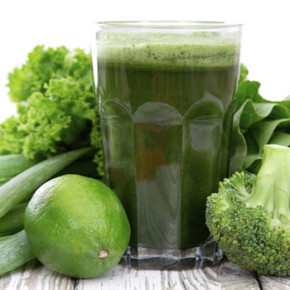 A green smoothie surrounded by green vegetables