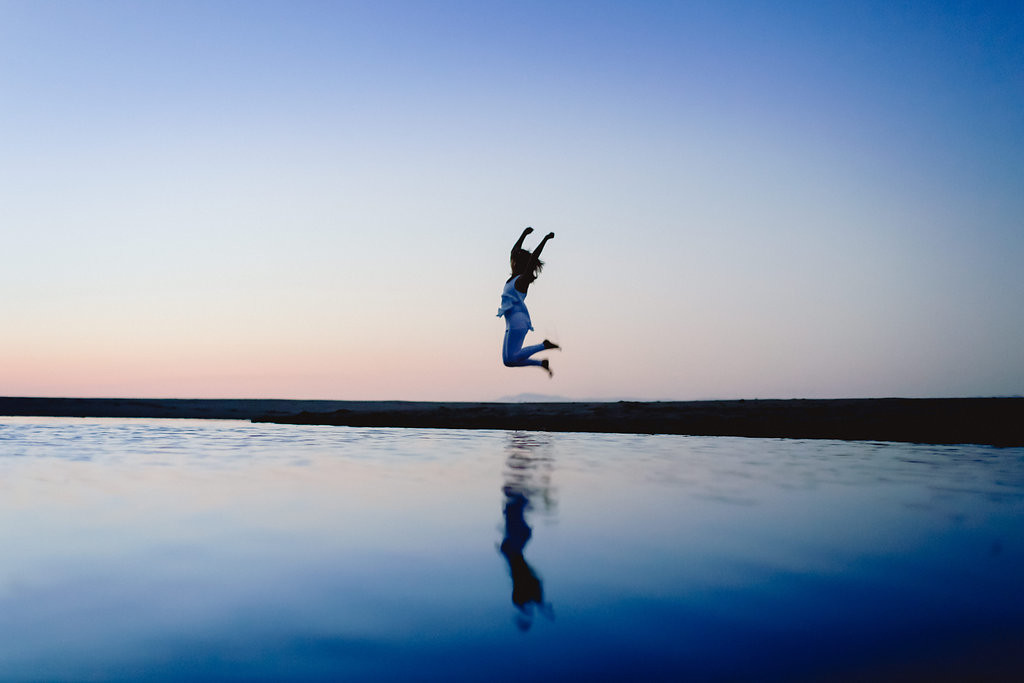 Melanee jumping in the air over the ocean water