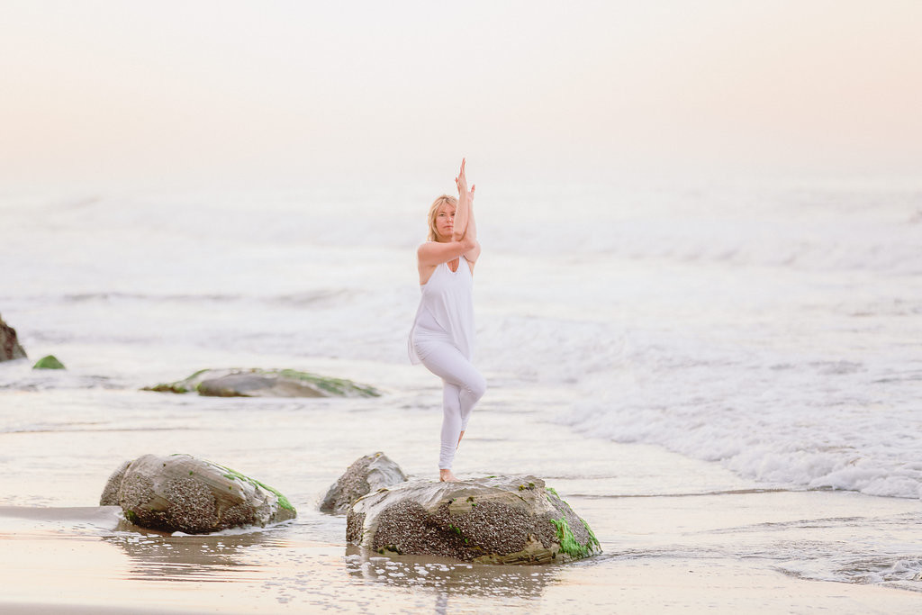 Melanee standing in Eagle Pose on a beach in Santa Barbara