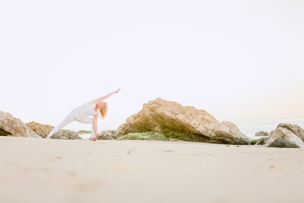 Melanee standing in Extended Side Angle Pose on the beach