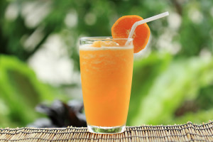Orange smoothie in a glass outside