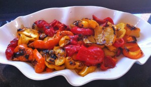 Grilled red and yellow peppers on a white wavy plate