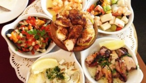 Many different plates with colorful seafood dishes on them