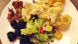Cauliflower with mixed greens and blackberries on a white plate