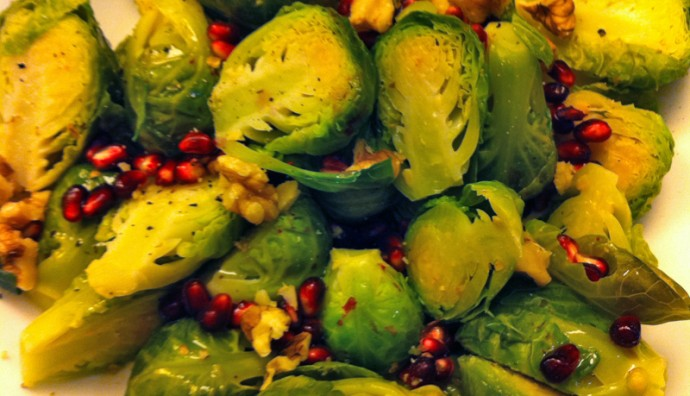 Steamed Brussels sprouts cut in half and sprinkled with pomegranate seeds and walnuts