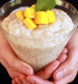Coconut and tapioca pudding with mango on top in a glass
