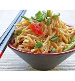 Asian noodles with vegetables and peanut sauce in a black bowl
