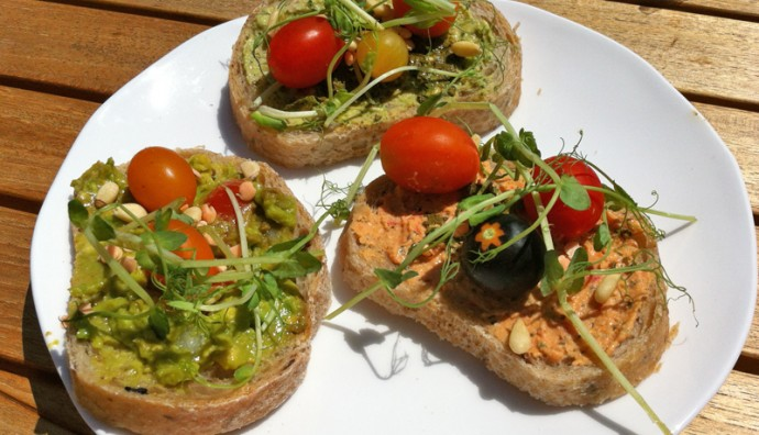 Three slices of bread with hummus, cherry tomatoes and greens on top