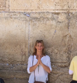 Melanee standing against a wall in Jerusalem with praying hands