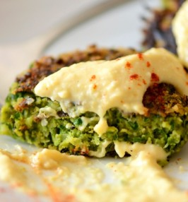 A green falafel piece with hummus on it
