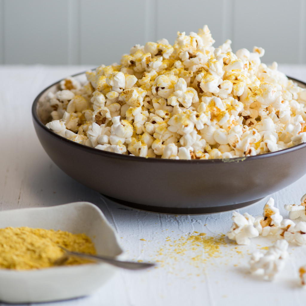 A big bowl of popcorn and a small bowl with nutritional yeast on a white table
