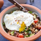 A bowl of quinoa with vegetables and a soft boiled egg on top