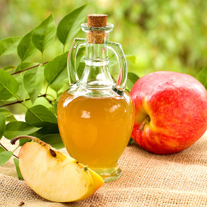 A small bottle of apple cider vinegar and a red apple