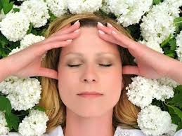 A woman's face surrounded by white flowers