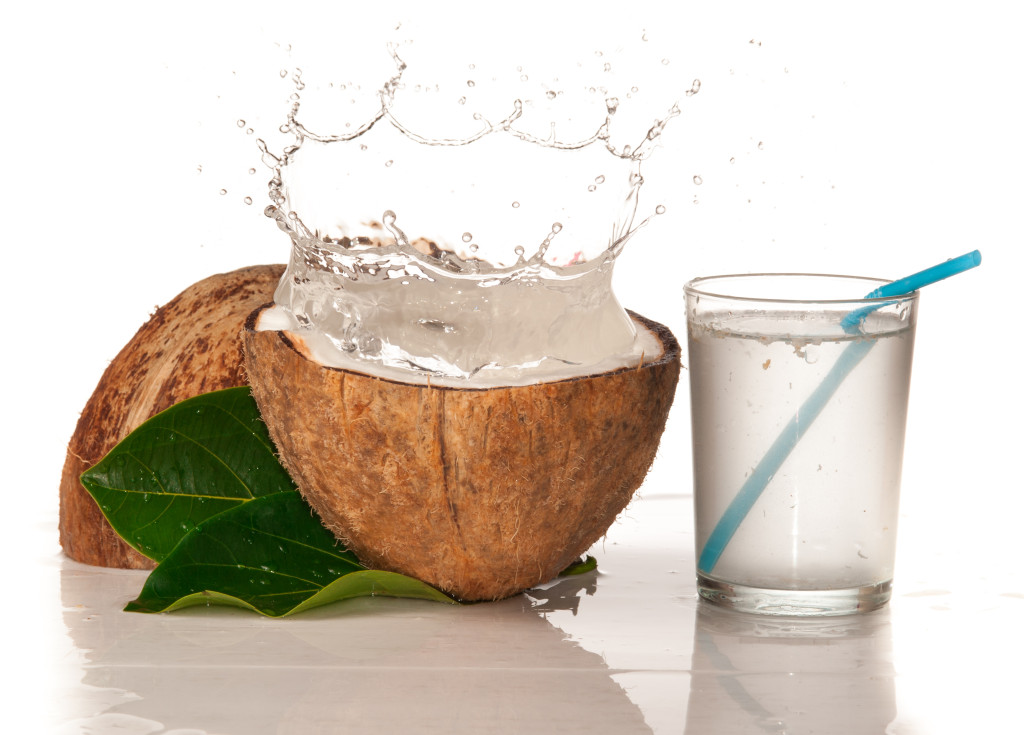 A glass with coconut water next to a coconut open in half