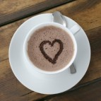 A cup of foamy hot chocolate with a heart drawn on top