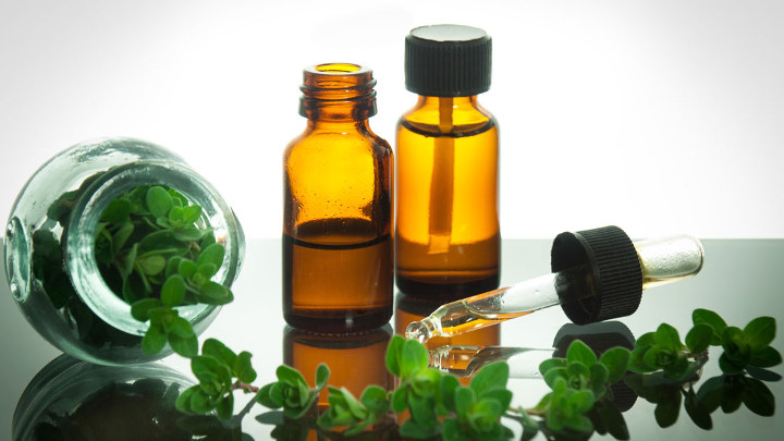 Two small bottles of oregano oil and a few oregano branches next to them