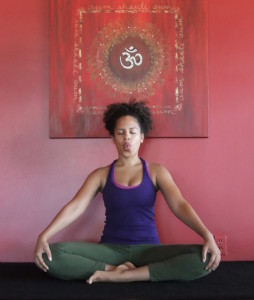 A woman sitting in the Lotus pose practicing Sitali breath