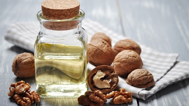 A small glass bottle with walnut oil and a few walnuts around it