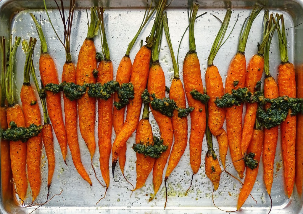 Baked whole carrots with pesto on a baking sheet