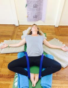 Melanee laying on a yoga mat in the Supported Bound Angel Pose