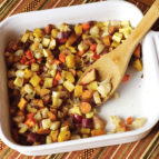 Roasted diced root vegetables in a white pan