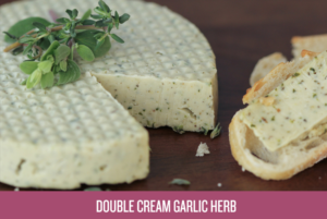 A cashew cheese wheel with green herbs on top