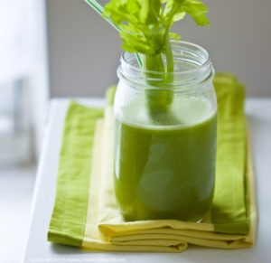 Green ginger celery juice in a small jar on a green kitchen towel