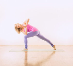 Melanee standing in the yoga pose Revolved Side Angle